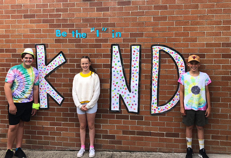 St John Bosco Catholic Primary School Engadine students standing in front of a 'Be the I in Kind' mural